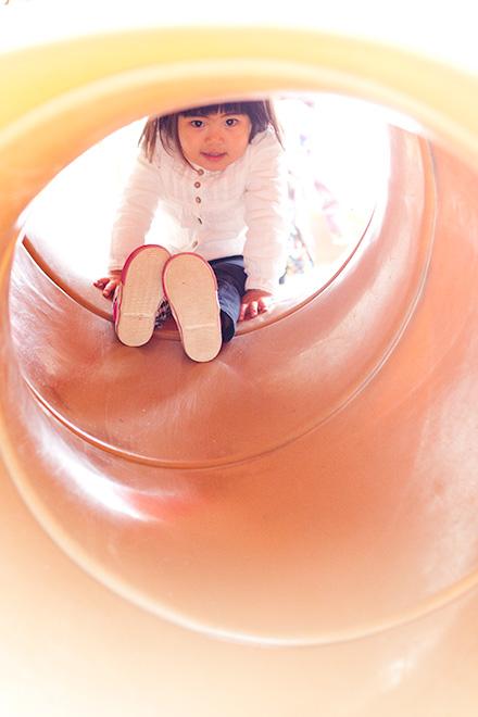 トンネルのすべり台を覗き込むお姉ちゃん