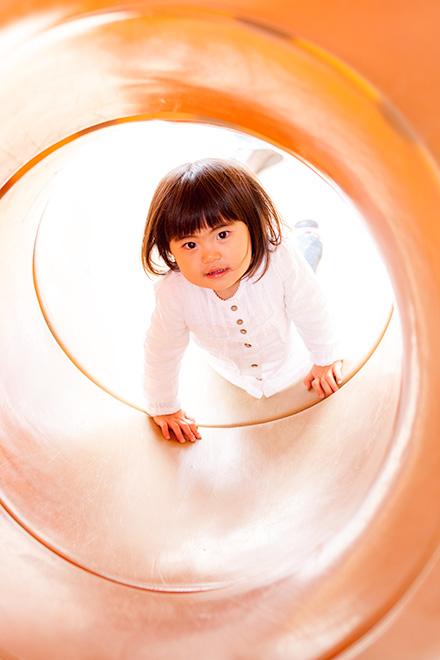 トンネルのすべり台を滑るお姉ちゃん