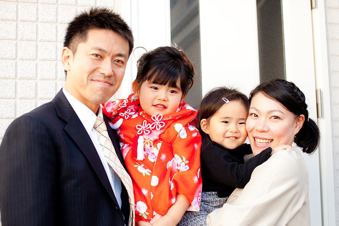 玄関の前で4人揃って家族写真