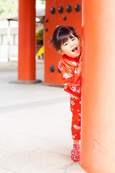三門の大きな赤い柱でかくれんぼする女の子