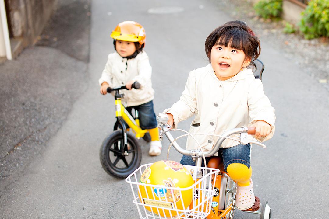 自転車に乗っておでかけする女の子と追いかける妹さん