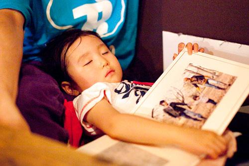 写真を抱えて眠る子供