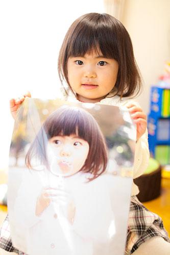 四切サイズの写真を持つ女の子
