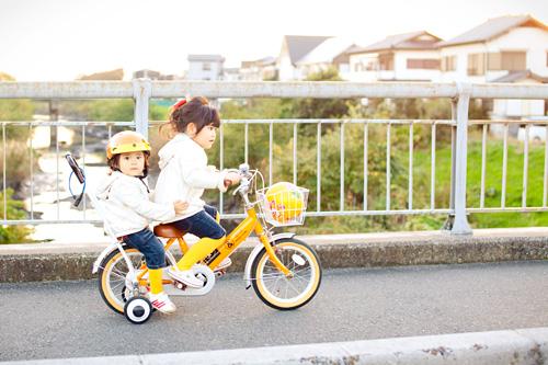 自転車に二人乗りする姉妹
