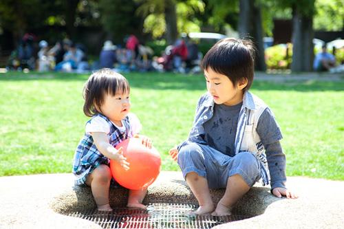 お池で並んで座る男の子と女の子