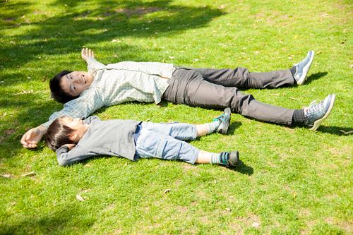 芝生に寝転がるお父さまと男の子