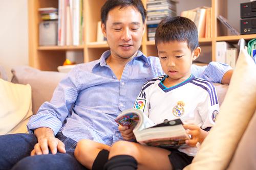 ソファで漫画を読む男の子とお父さま