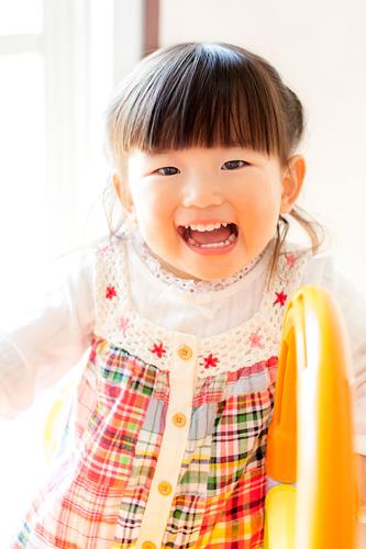 すべり台の上から笑う女の子