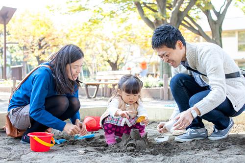 お砂場でお父さまとお母さまと遊ぶ女の子