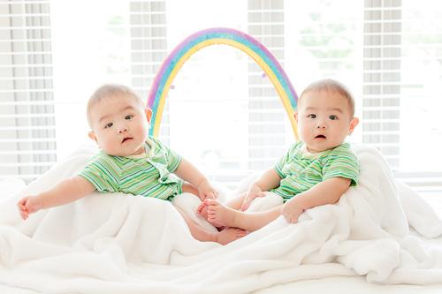 向かい合って座る男の子と虹