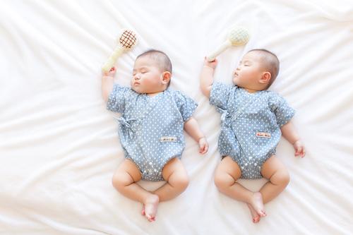 ラケットを持って眠る双子の男の子