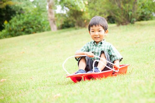 芝そり滑りをする男の子