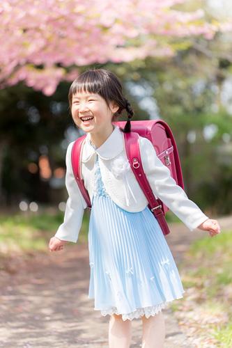 桜の下で楽しそうに笑う女の子