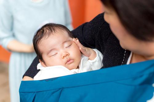 おばあさまの腕の中で眠る男の子